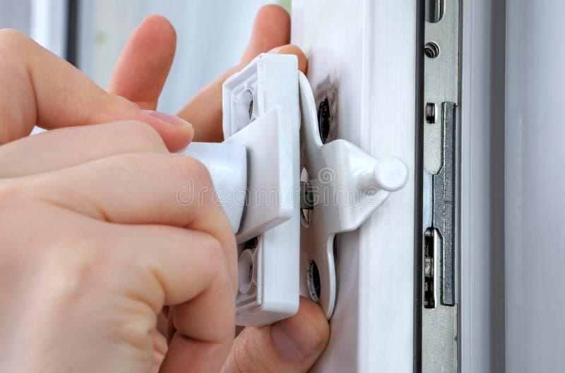 Närbildhänder av låssmeden som installerar fönsterlimiteren på plasti arkivbild