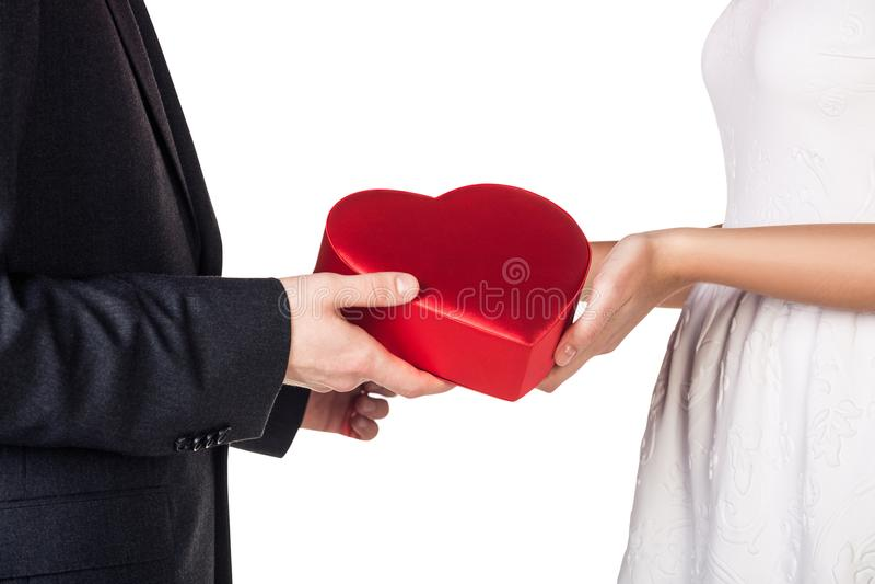 Närbildhänder av par som rymmer den röda gåvaasken arkivbilder
