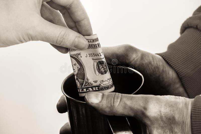Närbildhänder med koppen smutsar ner händer av en hemlös man för tiggare och en dollarräkning av allmosa royaltyfri bild