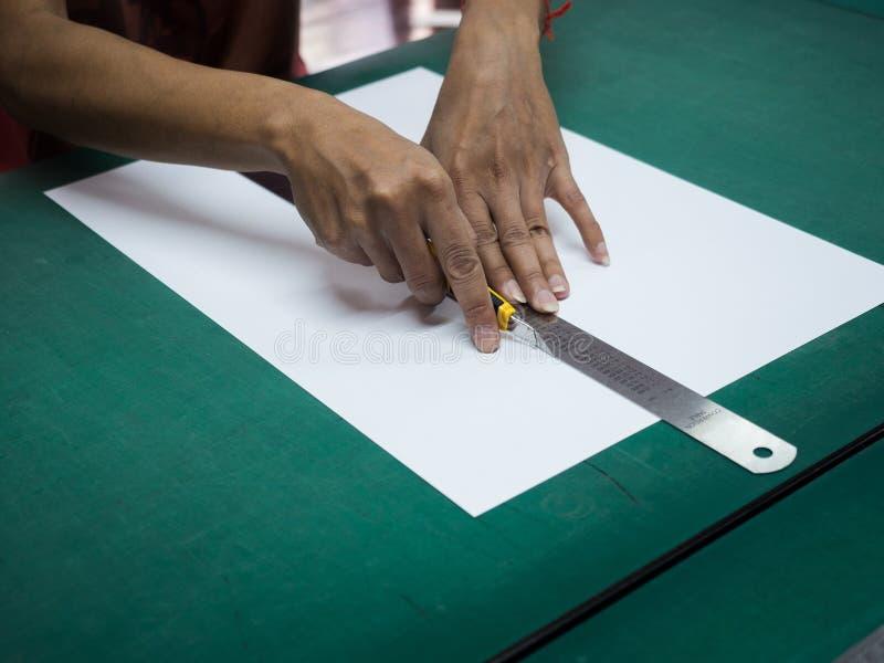 Närbildhänder som klipper vitbok med skärare- och järnlinjalen på grönt mattt arkivfoto