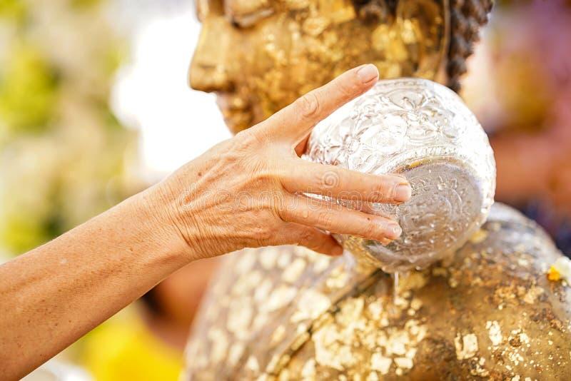 Närbildhänder som rymmer en bunke av vatten för att hälla Buddha i den Songkran traditionen Händer av hällande vatten för thai fo fotografering för bildbyråer