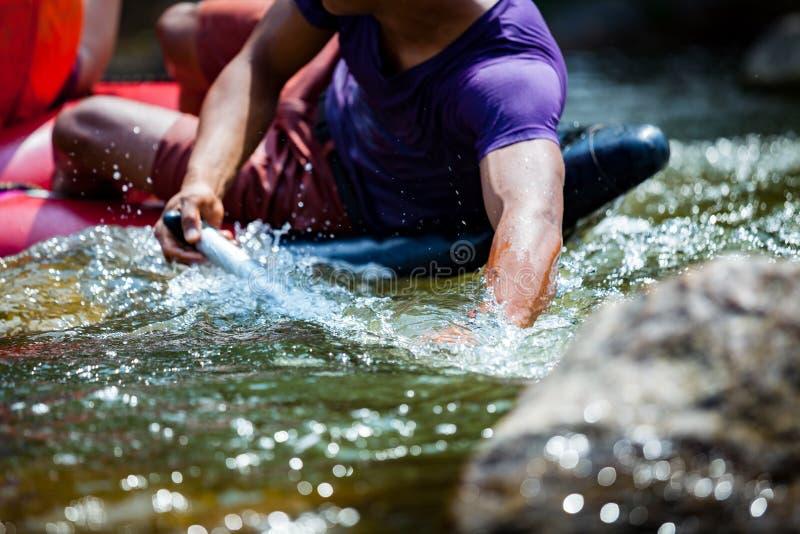 Närbildhanden av unga män rafting på floden fotografering för bildbyråer