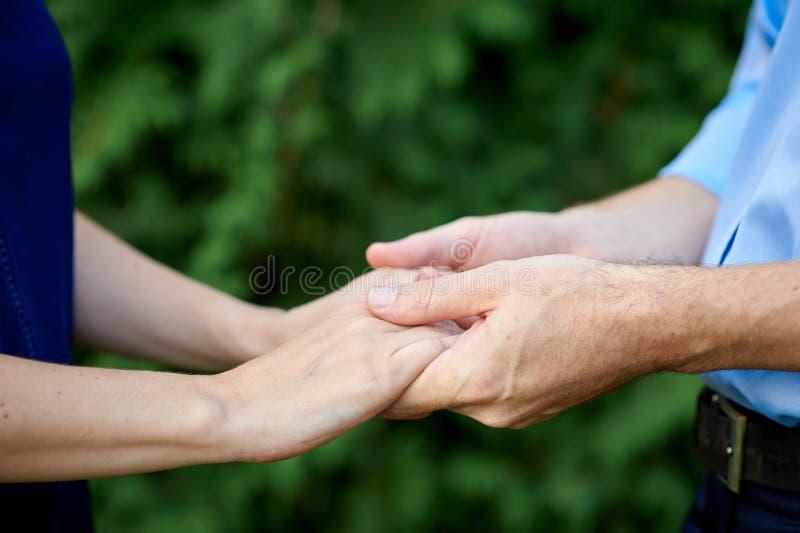 Närbildinnehavet räcker gifta par som rymmer händer royaltyfri bild