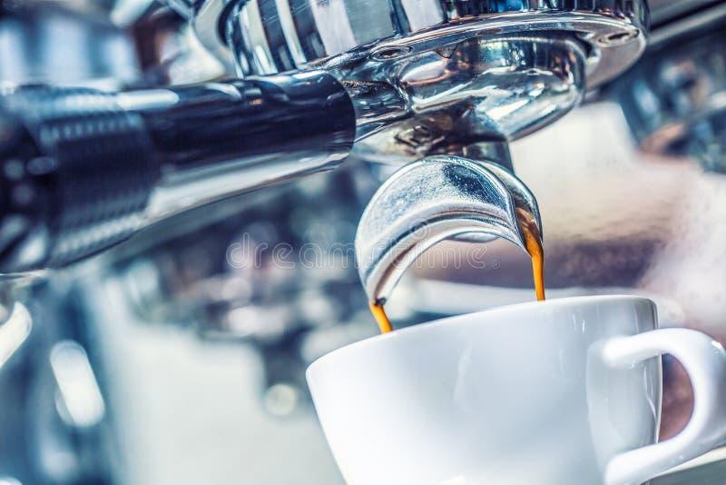 Närbildkaffemaskin som häller varm espresso fotografering för bildbyråer