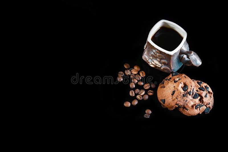 Närbildkoppen av espressokaffe, runda frasiga chokladkakor med kaffebönor på en svart bakgrund, makro, tömmer utrymme för t arkivfoton