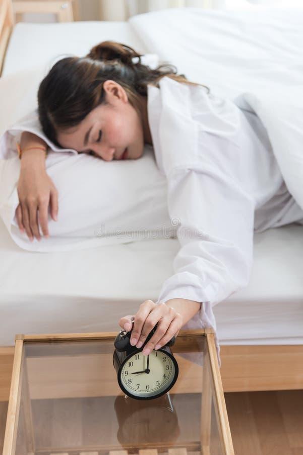 Närbildkvinna i säng hennes hand som är rörande av ringklockaextendin royaltyfria foton