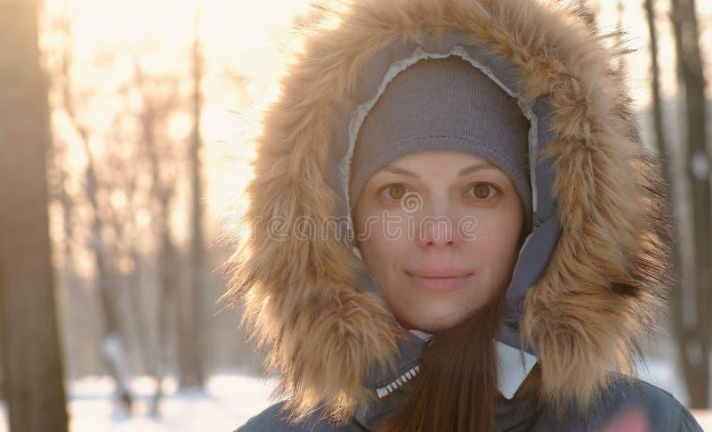 Närbildkvinnaframsidan i pälshuven som ser i den soliga vintern, parkerar in camera royaltyfri foto