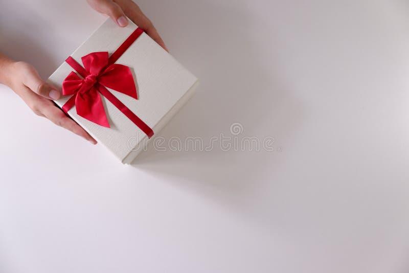 Närbildkvinnahänder som överför den vita gåvaasken med det röda bandet på vit bakgrund royaltyfria bilder