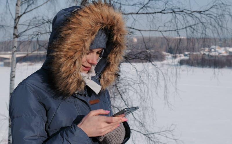 Närbildkvinnan i blått klår upp ner med pälshuven skriver messaging i hennes mobiltelefon i en vinter parkerar arkivbild