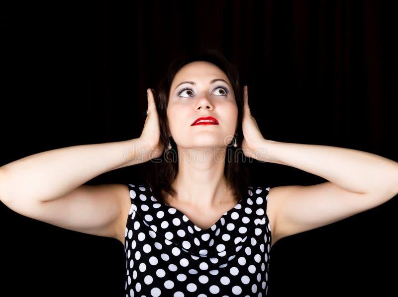 Närbildkvinnan ser rak in i kameran på en svart bakgrund när du skrattar kvinnan täcker hans öron med hans händer arkivfoton