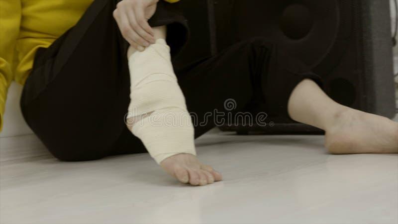 Närbildkvinnan som förbinder hennes ben med resår, förbinder actinium Oväntad skada eller sträckning av ankeln, medan öva arkivfoton