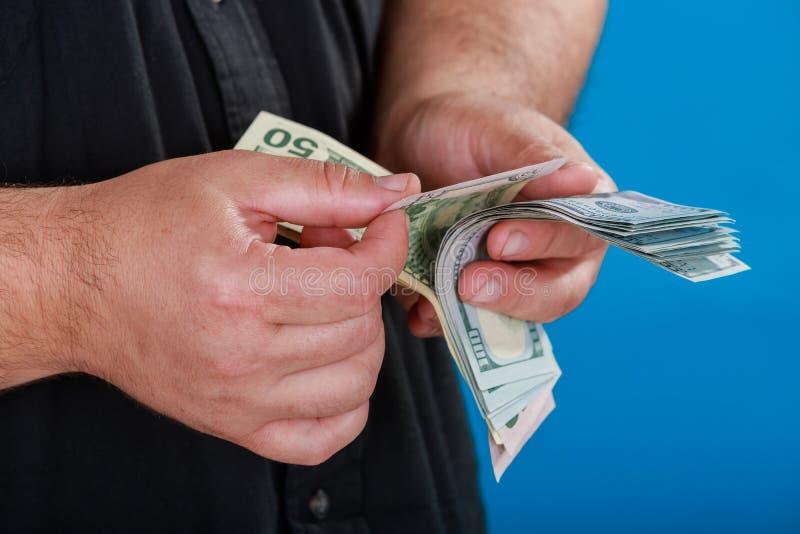 Närbildman som bär rymma USA hundra dollar en dräkt som räknar dollarräkningar arkivbilder