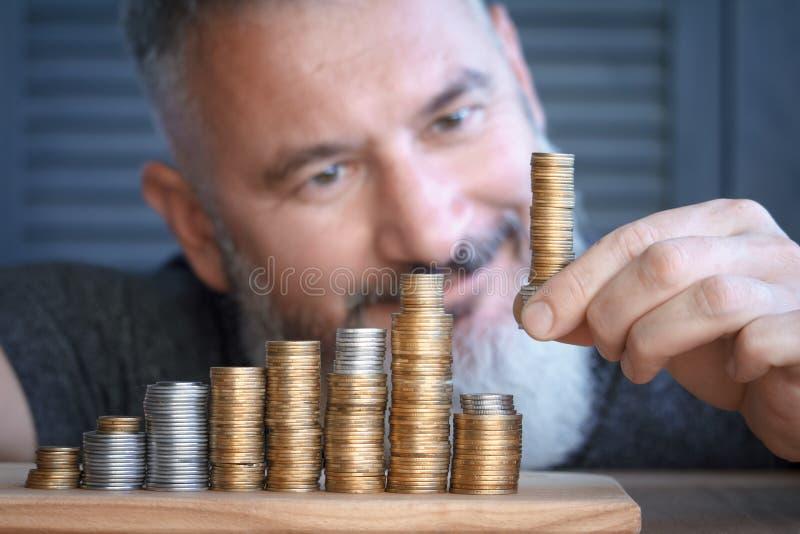 Närbildmannen samlar kolonner av mång--färgade mynt av ökande höjd, begreppet av ackumulations- och sparandepengar som är selekti royaltyfri foto