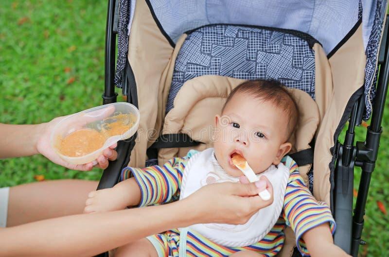 Närbildmoderhänder som matar mat för, behandla som ett barn på sittvagnen i gräsplan parkerar arkivbild
