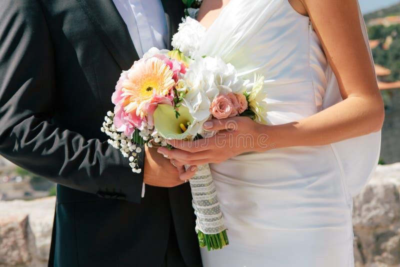 Närbildnygift personbrud och att ansa att krama och att rymma att gifta sig buketten i händer, selektiv fokus royaltyfri bild