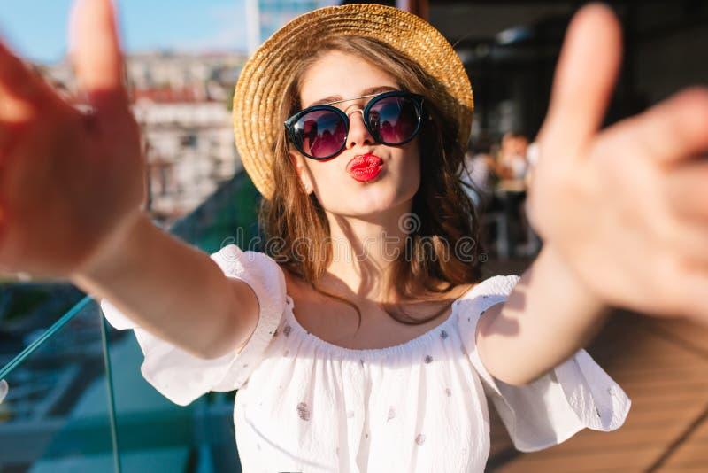 Närbildselfie-stående av den roliga flickan med långt hår som står på solljus på terrass Hon bär den vita klänningen, hatten som  royaltyfria bilder