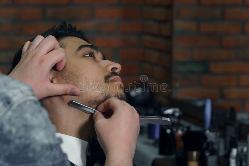 Närbildsidosikt av den unga skäggiga mannen som får skäggfrisyr av frisören på frisersalongen arkivbild