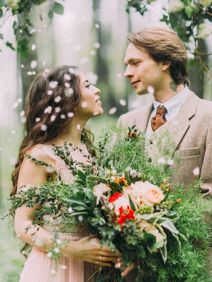 Närbildsidoståenden av de älskvärda nygifta personerna som ser in i de ögon och bruden, rymmer det enormt fotografering för bildbyråer