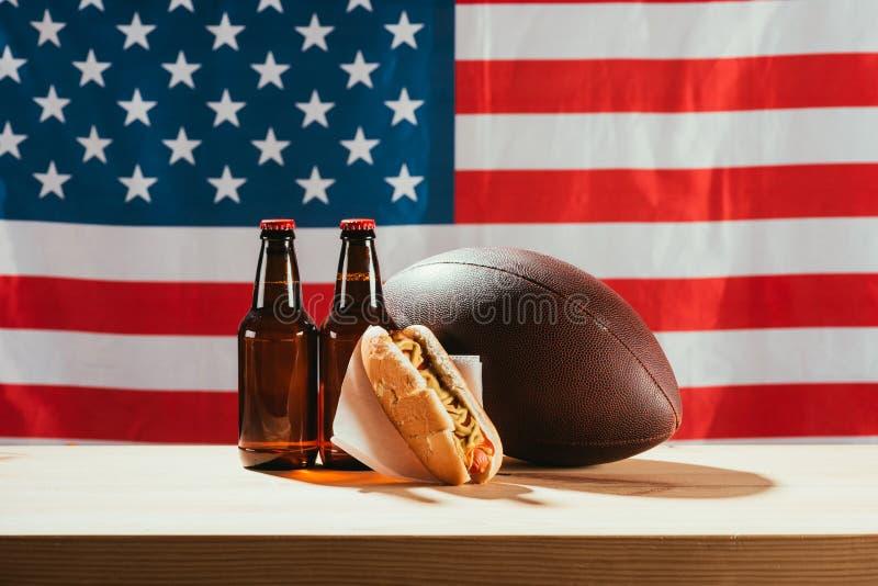 närbildsikt av ölflaskor, varmkorven och rugbybollen på trätabellen med oss royaltyfri fotografi