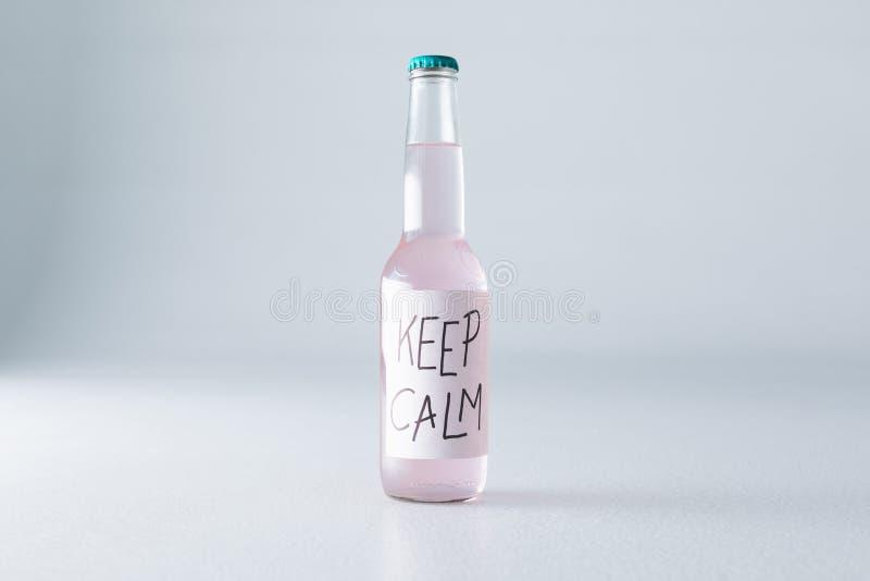 närbildsikt av alkoholdrycken i flaska med inskriftuppehällestillhet på etikett royaltyfri foto
