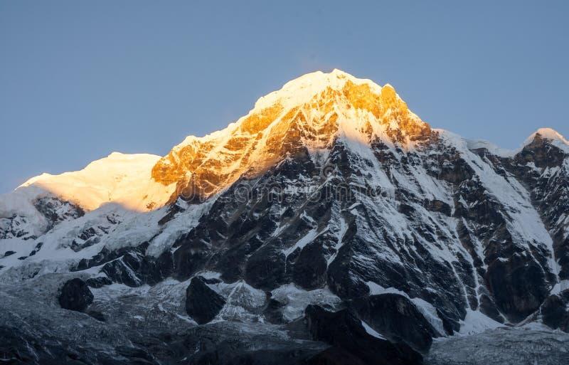Närbildsikt av Annapurna det södra montainmaximumet under guld- timme för soluppgång mot klar blå himmel, Nepal royaltyfria bilder