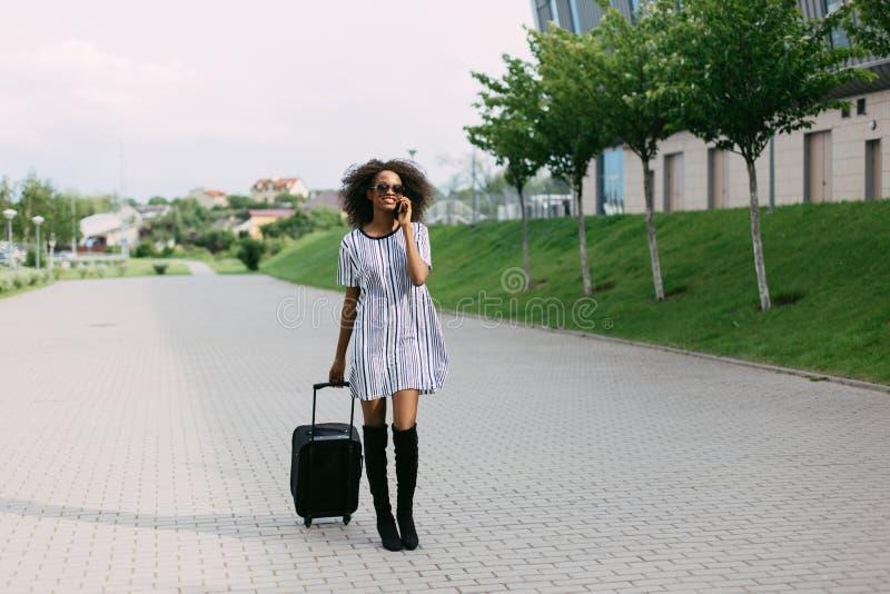 Närbildsikt av den härliga le afro--amerikan kvinnan som talar via mobiltelefonen, medan rymma bagaget fotografering för bildbyråer