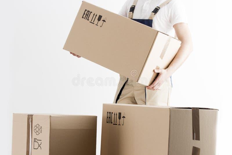 Närbildsikt av den hållande kartongen för flyttkarl som isoleras på vit bakgrund Begreppsnolla-förflyttning in i nytt hus boxes l arkivbilder