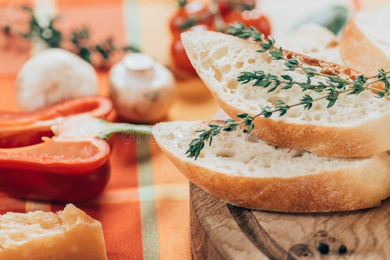 närbildsikt av den nya skivade bagetten på träskärbräda- och parmesanost med spansk peppar och champinjoner arkivfoton