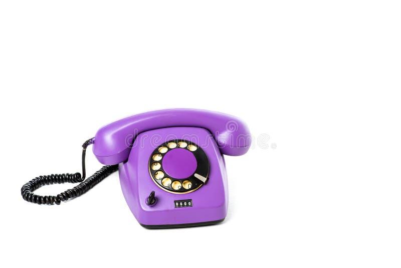 närbildsikt av den purpurfärgade roterande telefonen på vit royaltyfria foton