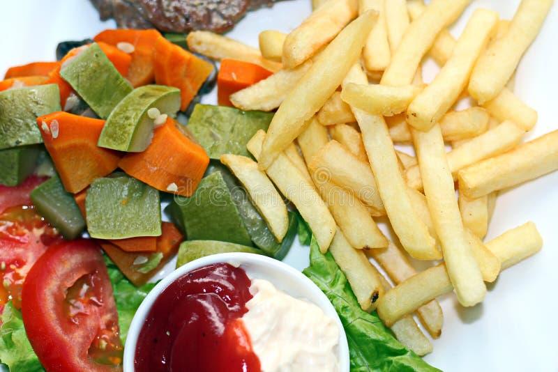 Närbildsikt av den stekte nötköttkött och fisken med potatisar och grönsaker som ligger på tabellen för lunch arkivbild