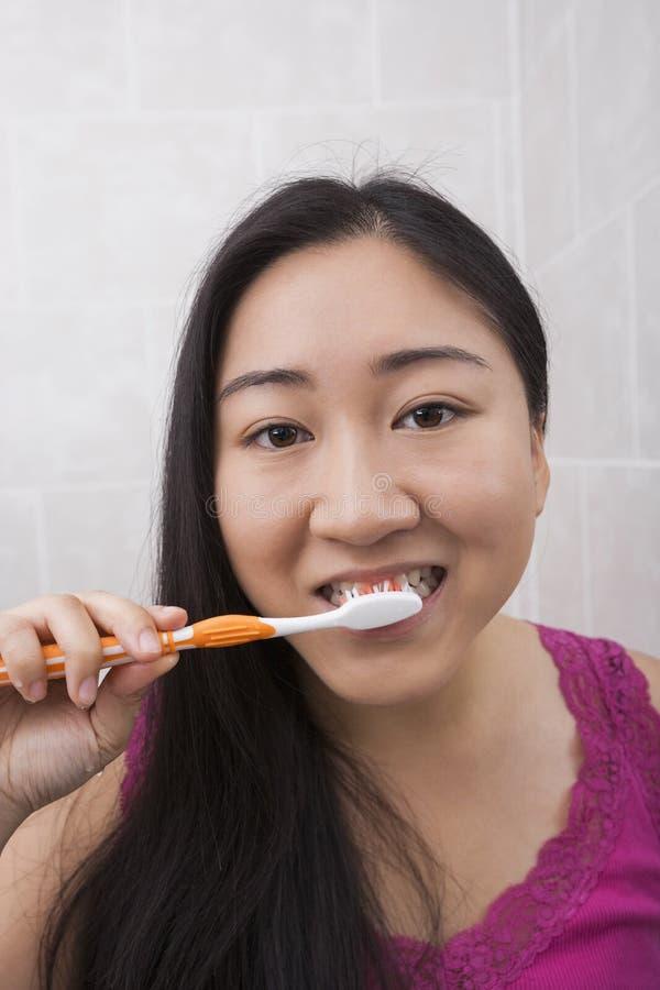 Närbildsikt av den unga asiatiska kvinnan som borstar hennes tänder i badrum royaltyfri bild