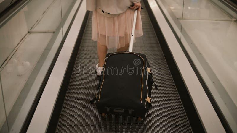 Närbildsikt av den unga kvinnan med resväskaanseende på rulltrappan i flygplats Hipsterkvinnlig som är klar till att gå att snubb royaltyfri foto