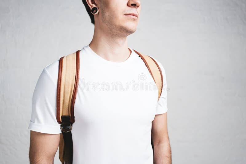 Närbildsikt av den unga stilfulla mannen som bär den tomma vita t-skjortan och ryggsäcken Hon är rädd royaltyfri fotografi