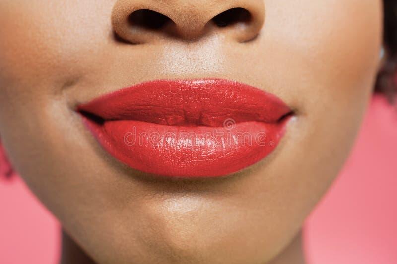 Närbildsikt av en afrikansk amerikankvinnas röda kanter över kulör bakgrund royaltyfri bild