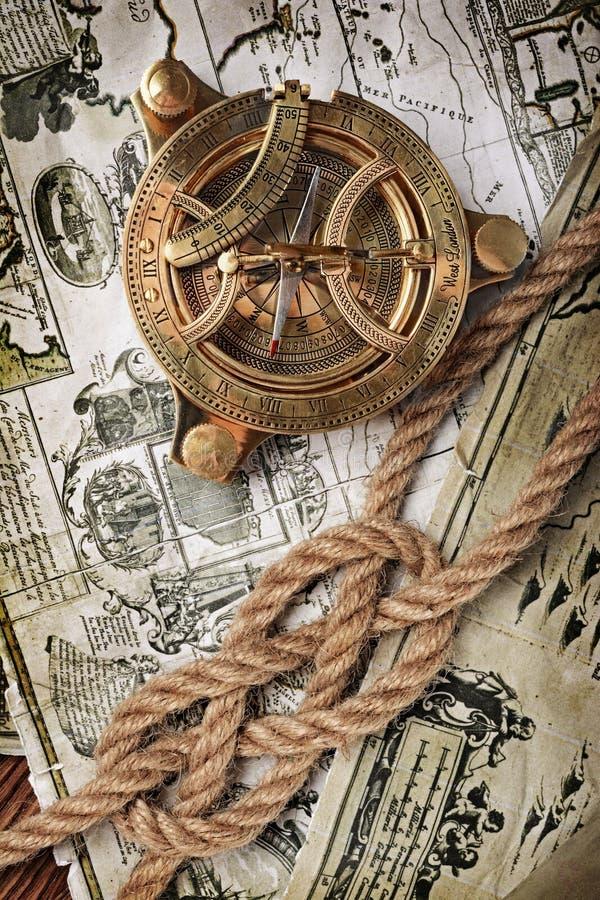 Närbildsikt av en tappningkompass och en fnuren av repet på en gammal retro översikt royaltyfri fotografi