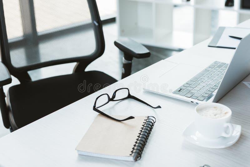 närbildsikt av glasögon, anteckningsboken, koppen kaffe och bärbara datorn på tabellen i regeringsställning arkivfoton