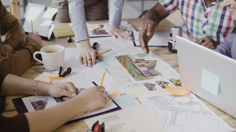 Närbildsikt av grupp människor för blandat lopp som arbetar på tabellen Lag som diskuterar den arkitektoniska designen, start-up  royaltyfria bilder
