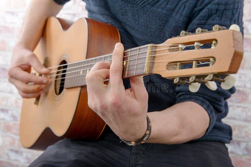 Närbildsikt av handen för man` som s spelar gitarren royaltyfri bild