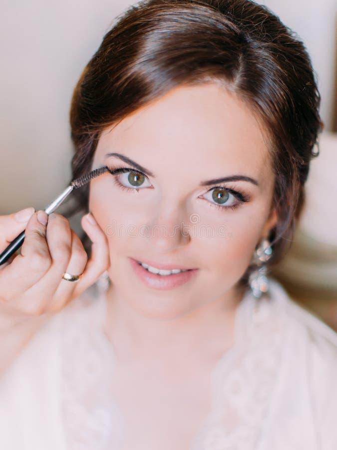 Närbildsikt av handen av makeupkonstnären som gör makeupen för bruden royaltyfria foton