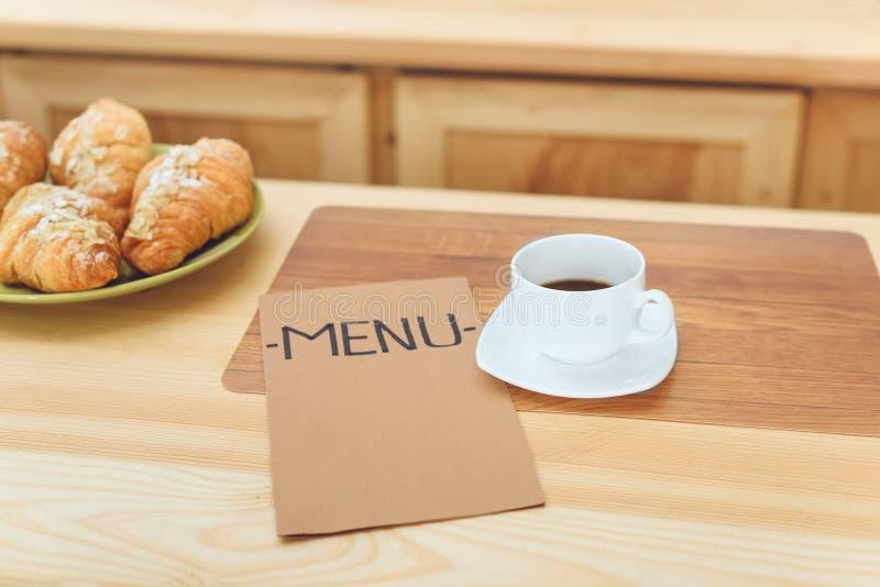 närbildsikt av koppen kaffe, menyn och giffel på tabellen royaltyfri fotografi