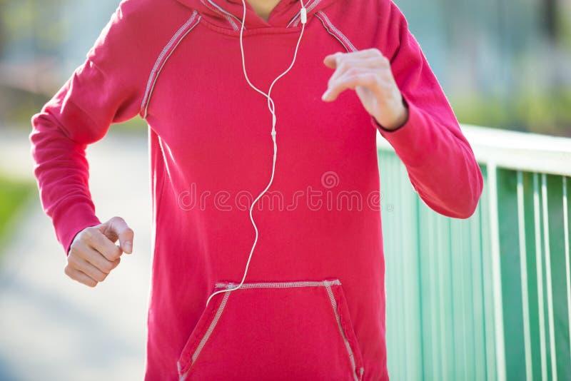 Närbildsikt av löparekvinnan som utarbetar på gatan arkivbild
