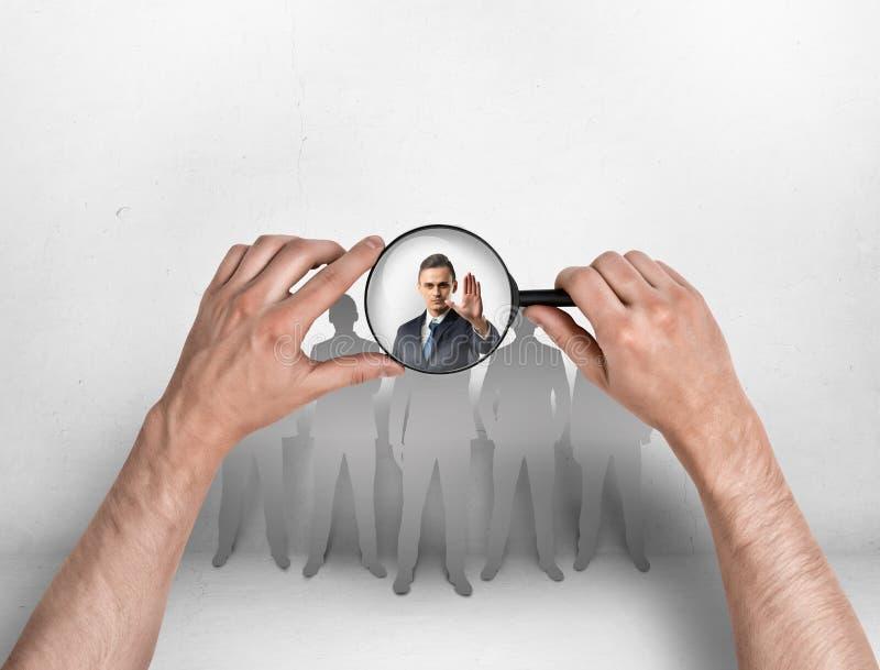 Närbildsikt av man& x27; s räcker att fokusera förstoringsapparaten på affärsman med hans lyftta hand royaltyfri foto