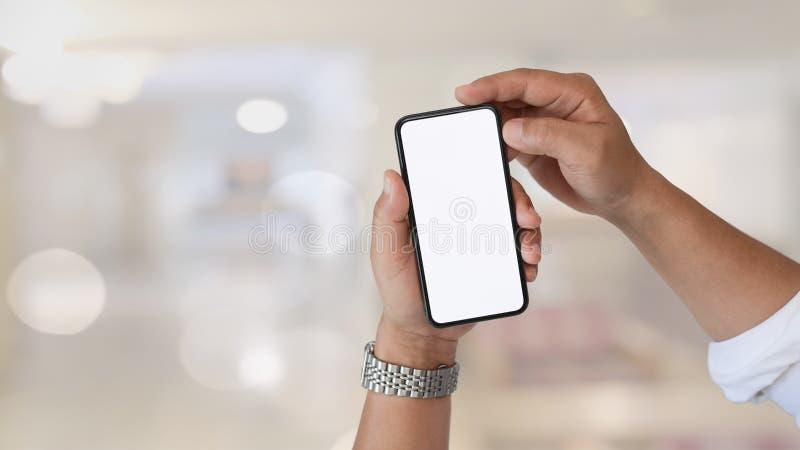 Närbildsikt av mans händer genom att använda smartphonen royaltyfri foto