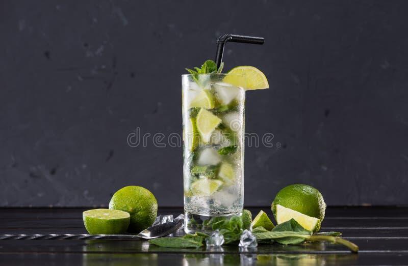 Närbildsikt av mojitococtailen i exponeringsglas, skivade limefrukter och mintkaramell på svart arkivbilder