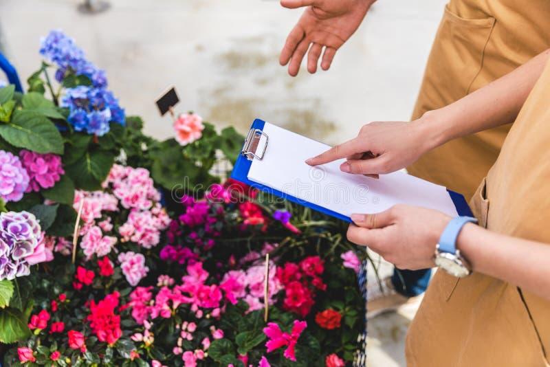 Närbildsikt av trädgårdsmästare med skrivplattan som diskuterar beställning royaltyfria bilder