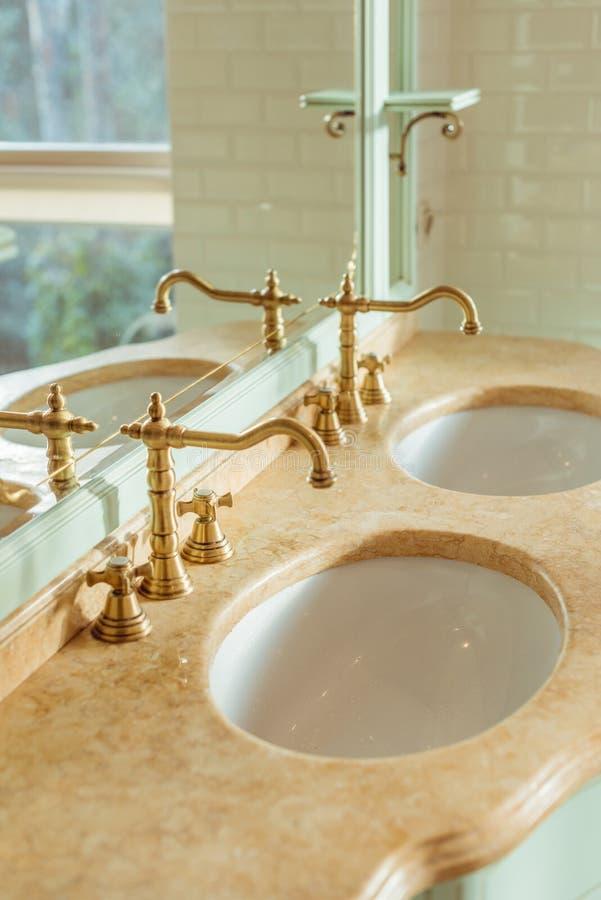 närbildsikt av två lyxiga vaskar och spegel royaltyfri bild