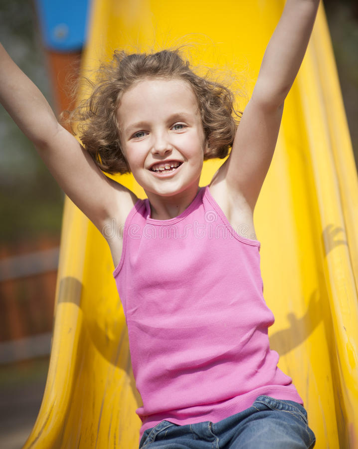 Närbildsikt av unga flickan på glidbana i lekplats royaltyfri bild