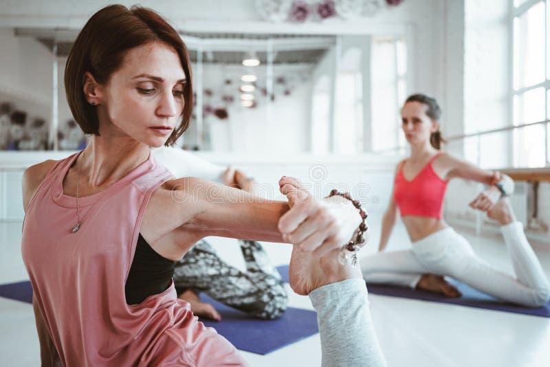 Närbildsikt på övande yoga för stark sund kvinna som är exerciese på kondition som är matt i vit sportgrupp royaltyfri bild