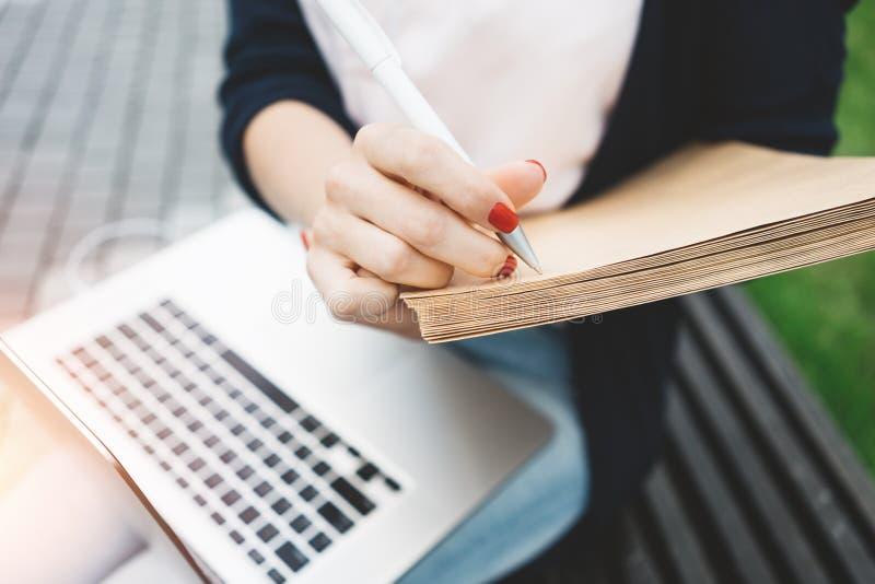 Närbildsikt på den kvinnliga studenten som förbereder sig för examina på det fria i stads- utrymme, bruksbärbar dator och pappers royaltyfri fotografi