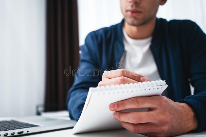 Närbildsikt på den manliga handen och notepaden som skriver affärsidéer på openspace arkivfoton